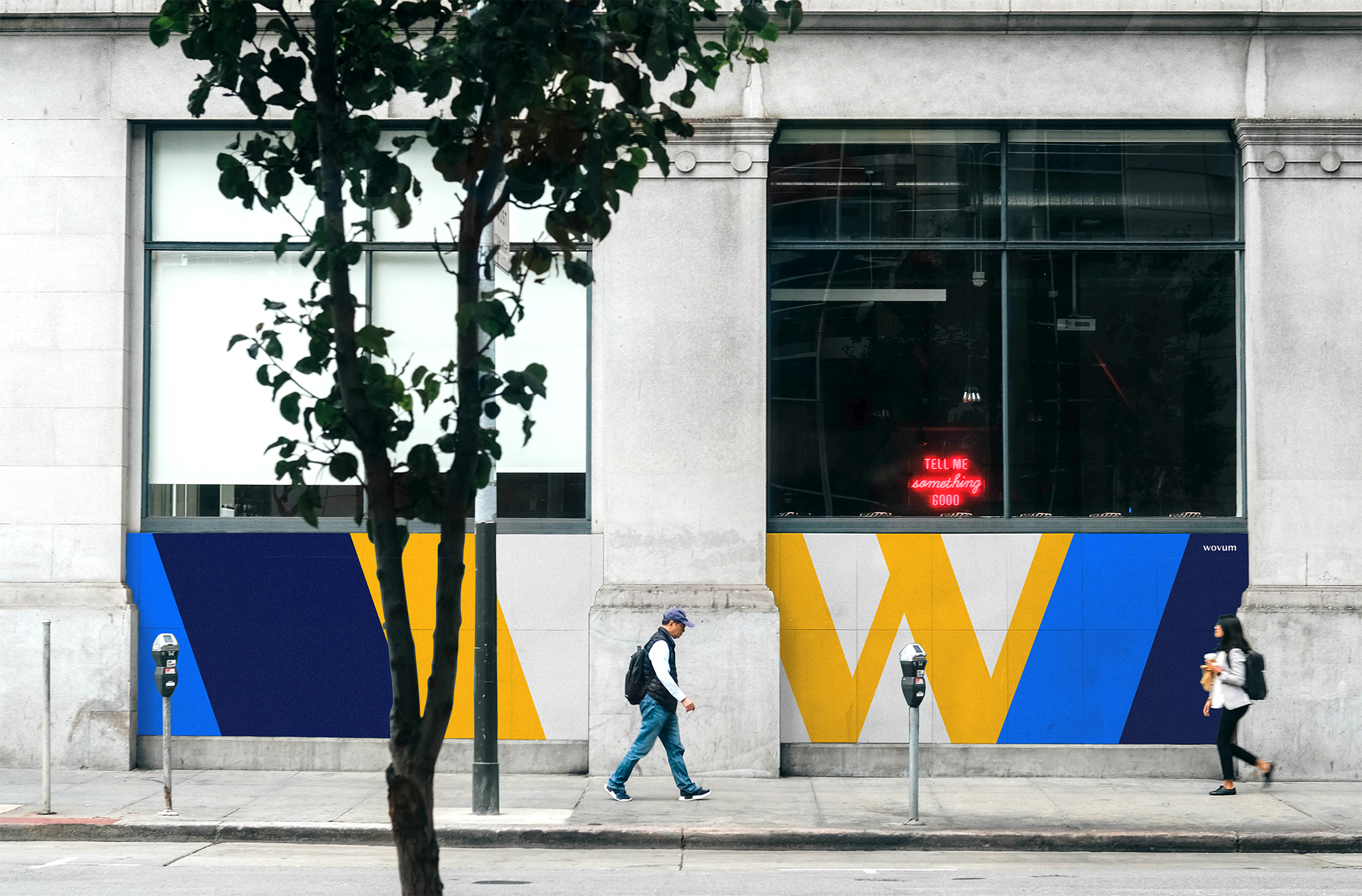 The image shows a photograph of wovum posters in an urban setting.