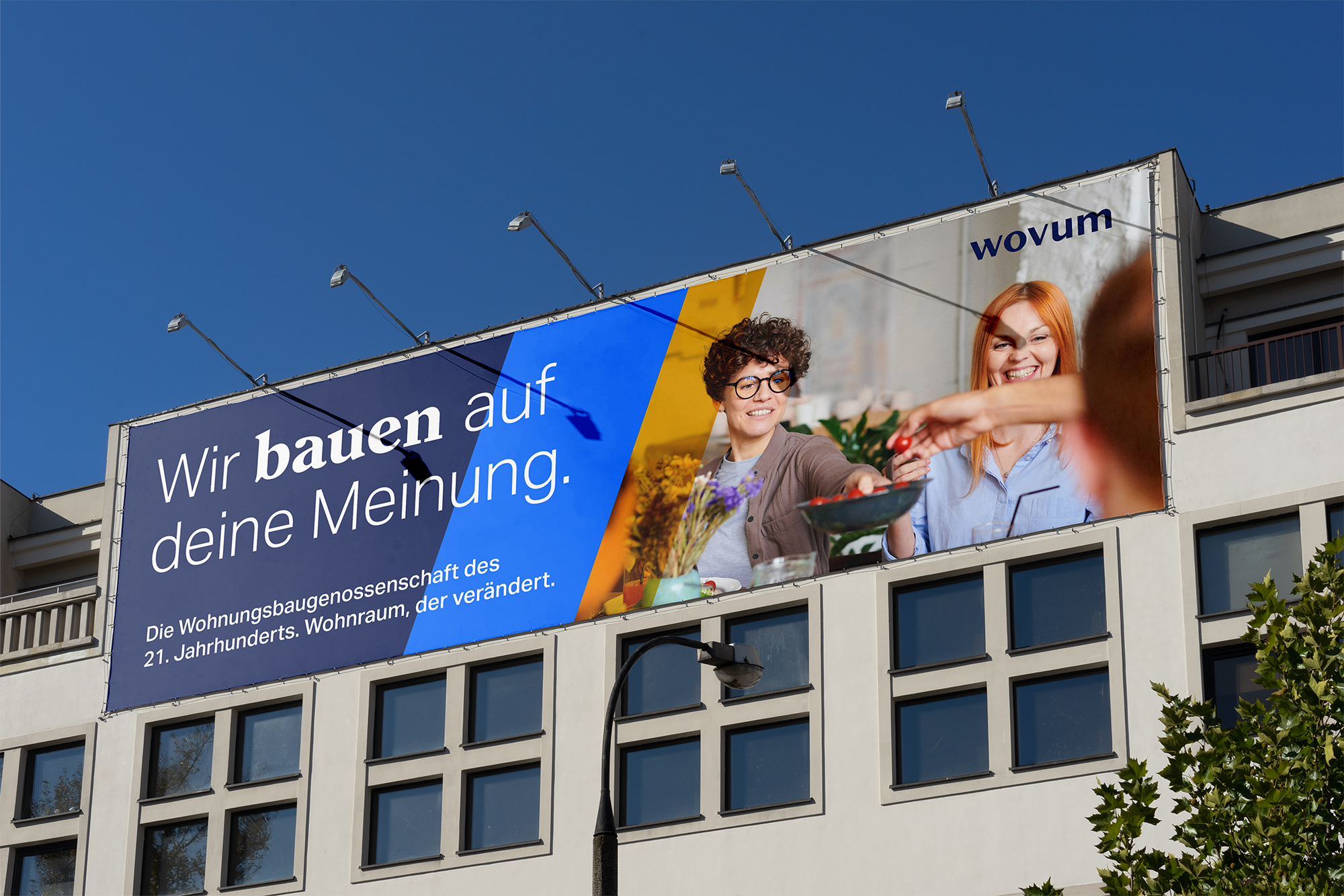 The image shows a photograph of a large wovum billboard in an urban setting.